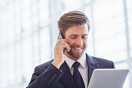 businessman speaking on phone and using tablet