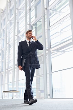 businessman talking on phone walking corridor