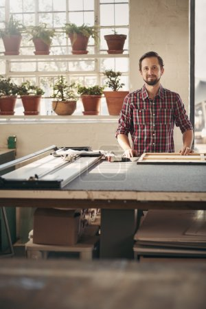Entrepreneur standing in studio at workbench