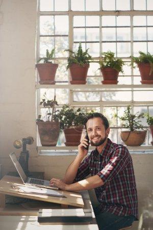 Entrepreneur smiling at camera from studio office