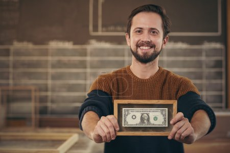 Entrepreneur showing framed bank note