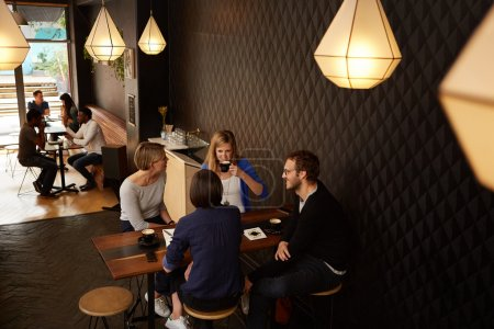friends sitting at table in modern cafe