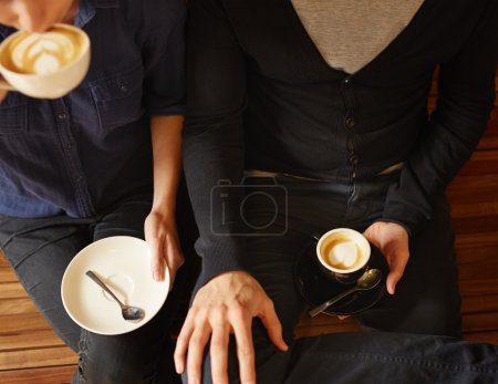 Photo for Overhead shot of the legs and hands of couple sitting on a wooden bench with coffee, the man holding espresso, while the woman is taking a sip of cappuccino - Royalty Free Image