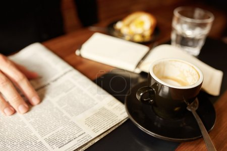 Photo for Cropped image of person reading a newspaper at a coffee shop, with a morning espresso and a notepad and pastry in the background - Royalty Free Image