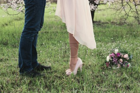 Beautiful legs of young girl in high heels next to the legs Man
