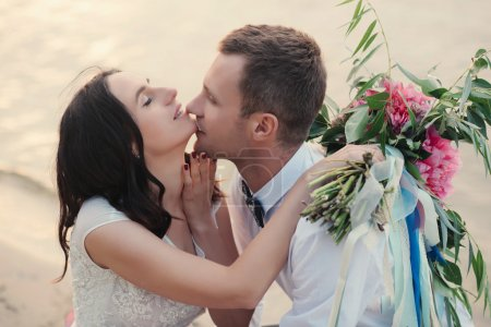 Kissing wedding couple in nature close-up portrait...