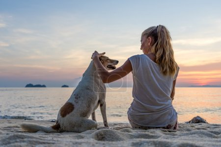 Young woman with dog sitting on the beach and watching the sunset