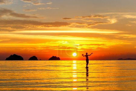 Silhouette of a man standing in the sea at sunset islands background on a tropical island