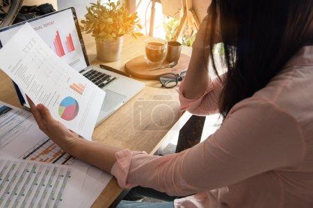 Photo pour Vue d'ensemble de la jeune femme au travail utilisant un ordinateur portable et lisant le rapport annuel au travail. Femme d'affaires travaillant à son bureau . - image libre de droit