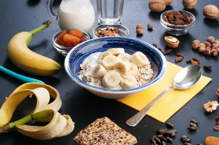 Useful and tasty breakfast with oatmeal, fruits, dried fruits and nuts on a dark surface. Healthy food concept. Useful vegetarian food