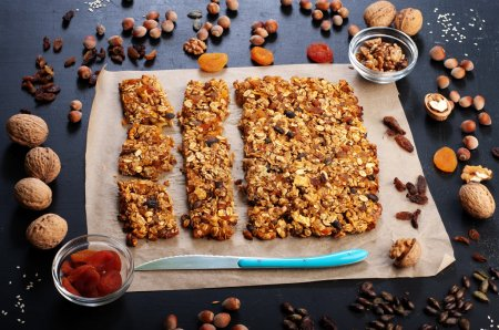 The concept of healthy delicious homemade dishes. Granola with nuts and dried fruits on a dark surface. Beside the ingredients for the preparation of granola, such as hazelnuts, walnuts, raisins and dried apricots