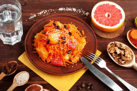 Concept diet food. Light salad with carrot, orange and grapefruit. Next to dried fruits and nuts, which are used in the preparation of a balanced diet. Vegetarian healthy food.