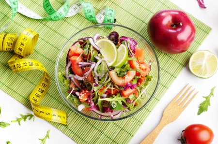 Photo for Concept diet food. Light salad of arugula, tomato, purple onion and lime on white background. Next measuring tape symbolizing measurement of body volume during a diet. Vegetarian low-fat food. - Royalty Free Image