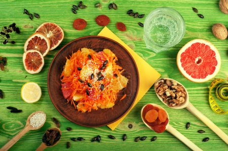 Concept diet food. Breakfast. Carrot-apple salad with dried fruit and nuts in a brown earthenware dish. Around half a grapefruit, nuts, raisins and a glass of water. Low-calorie dish that promotes weight loss. Green wooden background. View from above