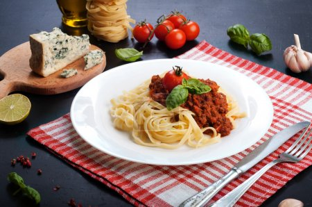 Pasta bolognese in white plate on a white and a red napkin. Beside the ingredients for making pasta. Italian Cuisine