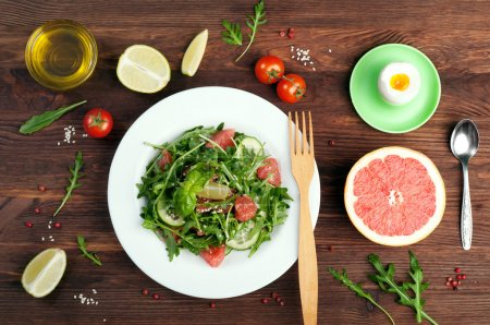 Concept diet food. Salad with arugula, slices of cucumber and a grapefruit on a dark surface. A variation on the classical diet with grapefruit and eggs. Brown wood background