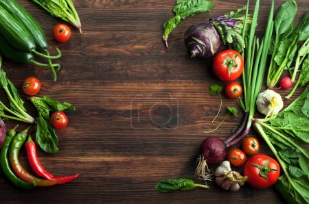 Photo for Fresh juicy vegetables and herbs, such as radishes, onion, spinach, tomatoes and hot peppers on a brown wooden board. Vegan concept. Vegetable background. Space for text - Royalty Free Image