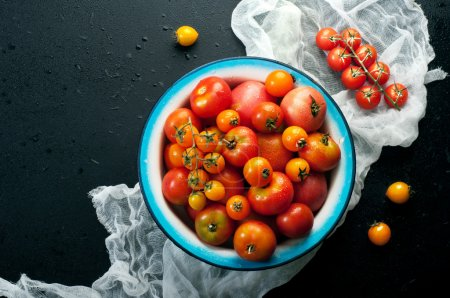 Plate with farm organic tomatoes of different colors and sizes on a black background.  Vegan concept. Vegetable background (wallpaper)