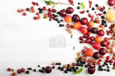 Summer berry background (wallpaper). Scattering of fresh ripe fruits and berries, such as gooseberries, cherries, red and black currants, peaches and plums on a white background. Place for writing text. Vegan concept