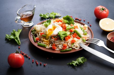 Egg noodles with fried vegetables on a plate of brown clay. Next to spices and herbs. Dark background, backlighting.
