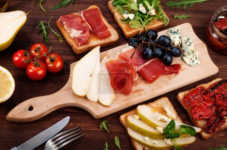 Sandwiches with various fillings, such as arugula, dried tomatoes, pear, blue cheese and ham on wooden background