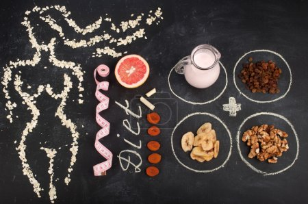 Photo for Concept diet food. Silhouette of a slender girl, laid oat flakes on a blackboard. Near diet foods that contribute to weight loss, such as grapefruit, yogurt and dried fruits. Vegetarian concept. - Royalty Free Image
