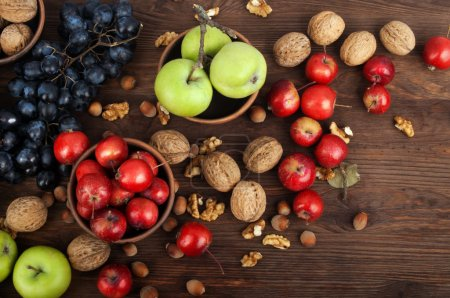 Still life with apples of different varieties, grapes and nuts on a dark wooden background. Vegetarian concept