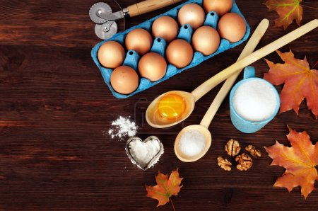Ingredients for cooking and cookware on a dark wooden background