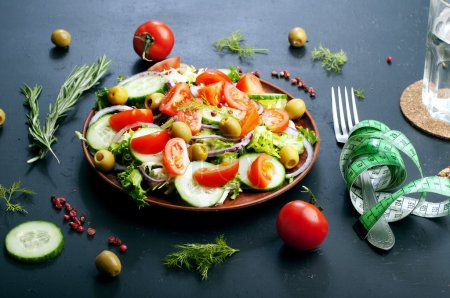 Concept diet food. Salad of fresh vegetables such as lettuce, purple onion, olives, cucumbers and tomatoes on a dark background. Vegetarian healthy dish