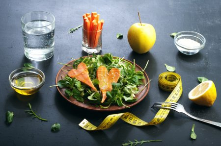 Concept diet food. Salad with arugula, leaf mash and carrots on a dark background. Vegetarian healthy dish that promotes weight loss.