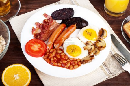 The classic English breakfast with fried eggs, sausages, black pudding, fried mushrooms and beans with tomatoes on a brown wooden background. The concept of a wholesome breakfast.