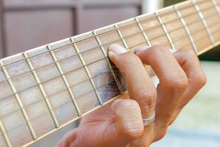 Guitarist hand playing acoustic guitar