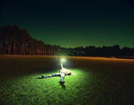 Man lying under night sky with light