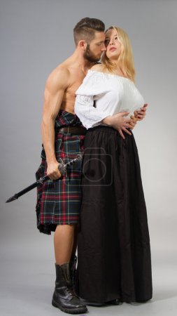 Photo for Couple posing in historical highland clothing. - Royalty Free Image