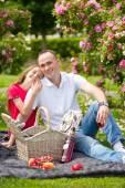 Bello giovane padre che si siede su un plaid in un parco verde con sua figlia graziosa piccola con un cestino di vimini per picnic felice