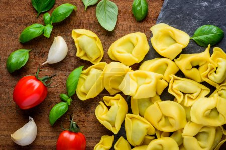 Photo for Yellow Tortellini Pasta with Green Basil Leaves, garlic cooking ingredients - Royalty Free Image
