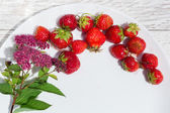 Jahody a květiny na bílé desce