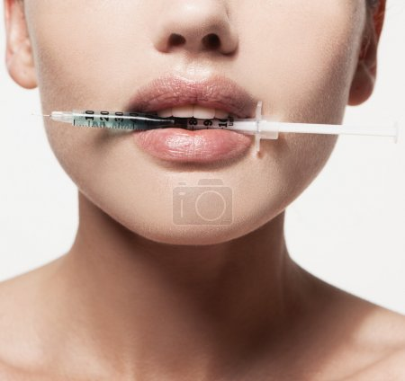woman with syringe in her mouth