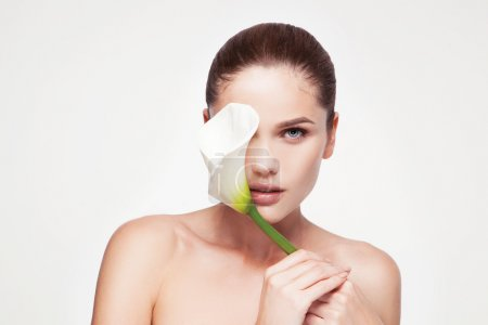 Photo for Beauty face of the young beautiful woman with flower. Girl on white background - Royalty Free Image