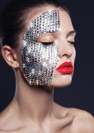 Foto de Hermosa joven modelo con labios rojos, con plata brillo en el rostro - Imagen libre de derechos