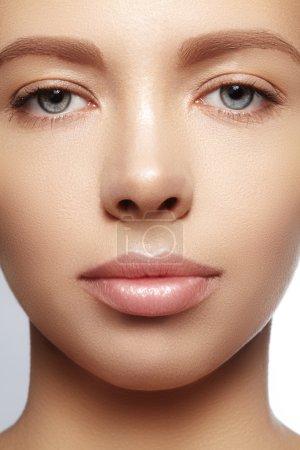 Foto de Hermosa joven con la piel limpia brillante perfecta, maquillaje de manera natural. Primer plano mujer, mirada fresca spa - Imagen libre de derechos