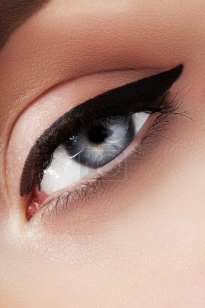 Photo for Close-up macro of beautiful female eye with perfect shape eyebrows. Clean skin, fashion naturel make-up. Good vision. Classic fashion eye liner makeup. Black eyeliner and brown eyeshadows - Royalty Free Image