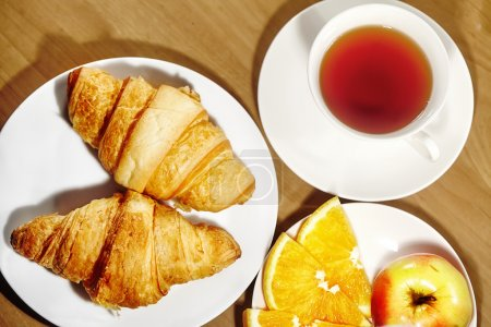 Photo for Backround continental breakfast with gold french croissants, fruits and cup of tea on wooden table. Great choice on morning. Tasty bread, vitamine orange and invigorating drink - Royalty Free Image