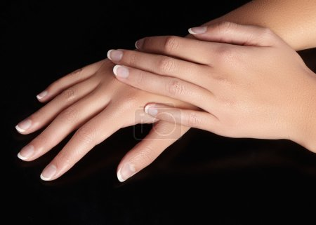 Beautiful female arms with ideal french manicure on black background. Care about female hands, healthy soft skin. Spa & cosmetics. Beauty care. Close-up of beautiful famele fingers with nails polish