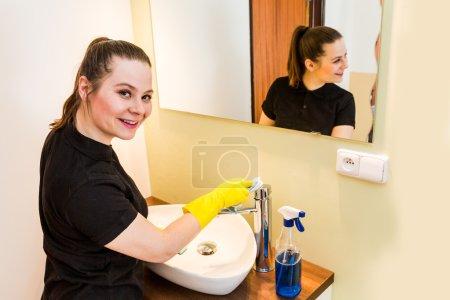 Photo pour Membre du personnel de ménage au travail dans la salle de bain - image libre de droit