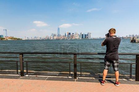 Photo pour Un homme prenant des photos de Manhattan, New York pendant une belle journée - image libre de droit