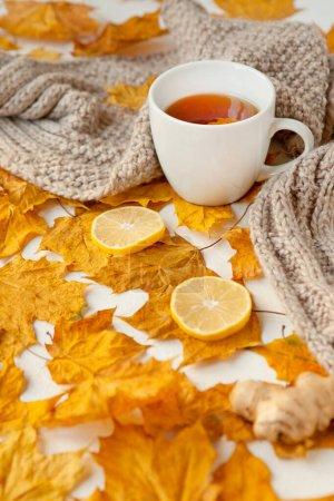 Photo pour Nature morte d'automne avec une tasse de thé blanc, une écharpe grise chauffante et des feuilles jaunes colorées au gingembre et au citron. Concentration sélective, peu profonde. - image libre de droit