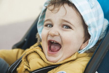 Close up portrait baby boy with big green eyes roar with laughte