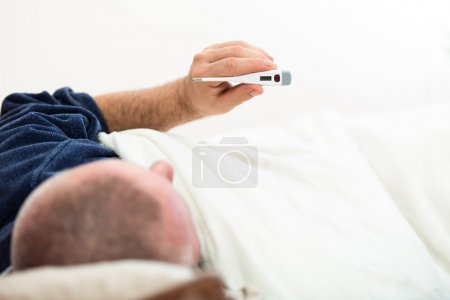 Dramatic image of a sick man laying in bed with fever