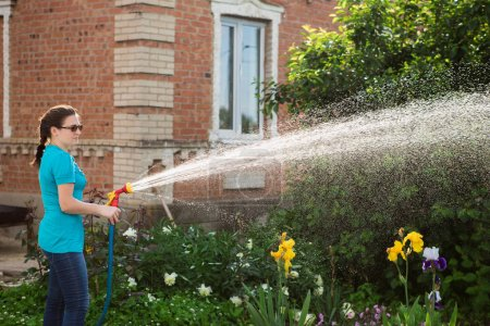 Woman watering garden at summer